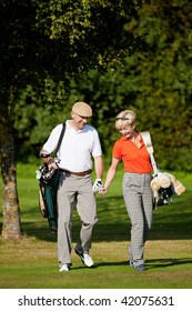 Mature or senior couple playing golf, walking down the course