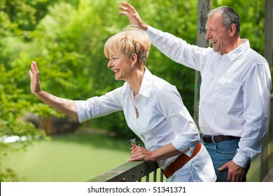 Mature or senior couple at a summer day standing on a bridge waving their hands as if to say goodbye to somebody