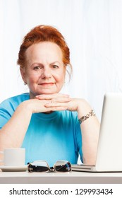 Mature senior lady in her 60s sitting with laptop and smiling