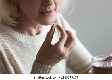 Mature senior middle aged woman holding pill and glass of water taking painkiller to relieve pain, medicine supplements vitamins, antibiotic medication, meds for old person concept, close up view