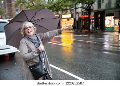 Mature senior white haired woman waiting for taxi cab in New Yor