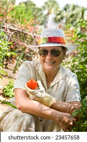Mature, senior woman in her backyard garden, holding the first tomato of the season.