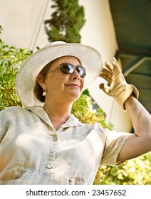 Mature, senior woman in sunhat and gardening gloves greeting the sunny day with enthusiasm