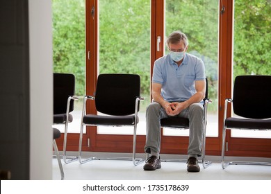 Mature serious patient or visitor alone sitting in an empty waiting room of an office or hospital
