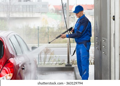 Mature serviceman with high pressure water jet washing red car at service station