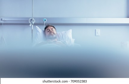 Mature sick male patient sleeping in hospital bed. Patient waiting for his health recovery in hospital ward.