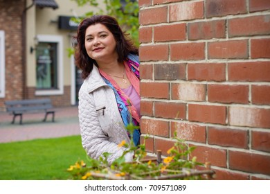 Mature simple woman of plus size, American or European appearance walks in the city enjoying life. Cute lady with excess weight, dressed in jacket and scarf going around old part of town