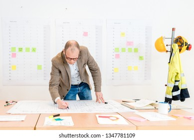 Mature skilled contractor making architectural plan on document in conference room