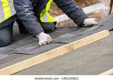 Mature and skilled workman in uniform work wear installing asphalt or bitumen tile on top of the roof under construction house