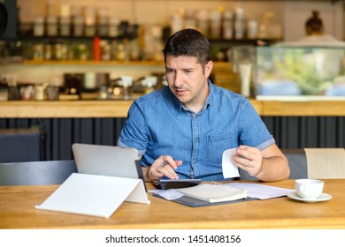 Mature small business owner calculating finance bills of activity – Entrepreneur using laptop and calculator to work and to calculate and analyze financial expenses of new business start-up
