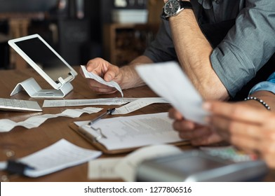 Mature smalll business owners calculating finance bills of their activity. Business people using calculator to work. Closeup hands of man and woman calculating bills and expenses.