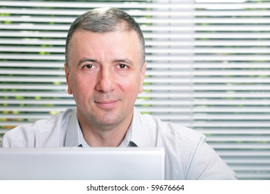Mature smiling business man in office