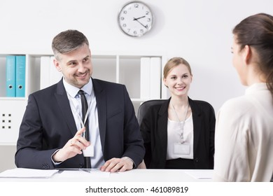 Mature smiling businessman gesturing at young woman at office