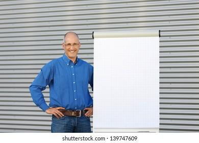 Mature smiling businessman making presentation on flipchart