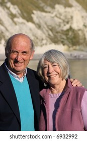 Mature smiling couple with sea and coast in the background.