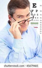Mature smiling man with  eyeglasses and eye chart