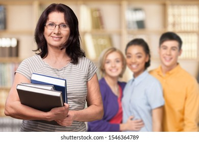 Mature smiling woman with books, teacher and students