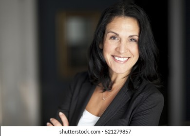 Mature Spanish Businesswoman Smiling At The Camera. At The Office.
