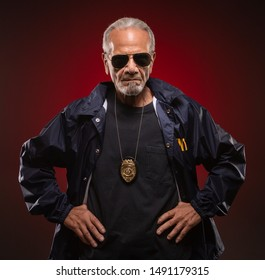 Mature special agent wearing sunglasses and a badge, with his hands on his hips.