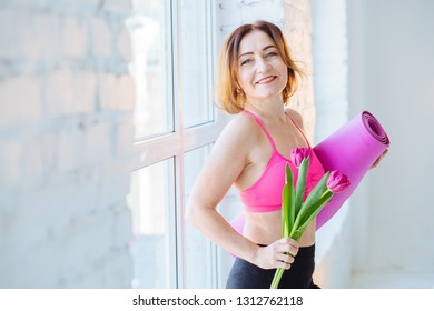 Mature sports female holding bouquet pink tulips flowers and mat after a good training session over white loft background. Senior caucasian woman get ready to start workout. Mood spring concept.