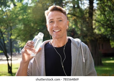 Mature sporty man drinking cool water outdoors