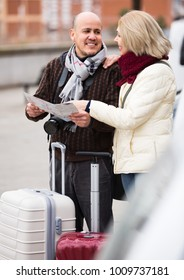 Mature spouses with baggage and paper map outdoors