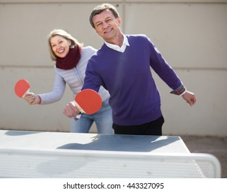 mature spouses playing table tennis outdoors