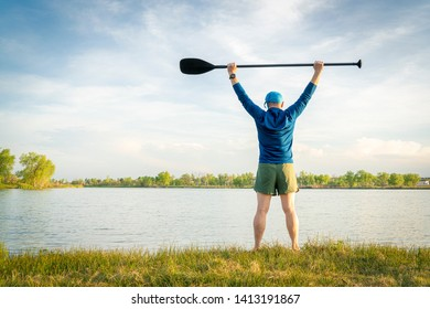 mature stand up paddler is stretching and warming up on a lake shore before paddling workout