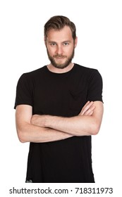 Mature staring man with beard wearing a black t-shirt standing against a white background looking at camera.
