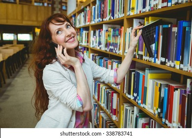 Mature student in the library using phone at the university