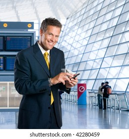 Mature successful businessman text messaging on mobile at the airport