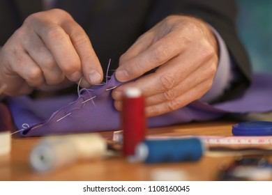 Mature tailor sewing at table in atelier, closeup