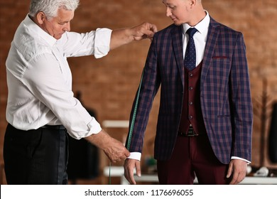 Mature tailor taking client's measurements in atelier