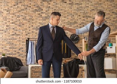 Mature tailor taking client's measurements in atelier