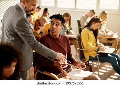 Reife Lehrer und afroamerikanische Schüler sprechen über Testergebnisse in der Vorlesungshalle. Der Fokus liegt auf den Schülern.
