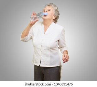 Mature Thirsty Woman Drinking Water On Gray Background