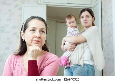Mature thoughtful woman against her adult  daughter with little baby  at home