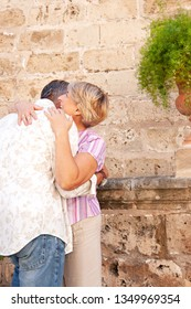 Mature tourist couple hugging joyful together visiting monument stone texture wall on holiday, outdoors. Senior man and woman sightseeing, enjoying fun retirement leisure recreation lifestyle.