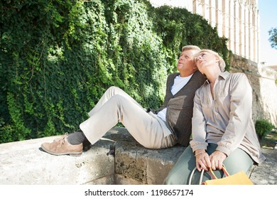 Mature tourist couple sitting relaxing sightseeing monument on vacation trip, serene in sunny outdoors. Senior man and woman enjoying city break travel, leisure recreation lifestyle.