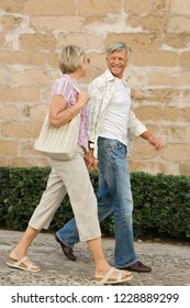 Mature tourist couple visiting city monument stone wall on holiday, walking together holding hands, smiling outdoors. Travel city break recreation leisure lifestyle.
