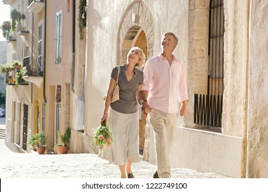 Mature tourist couple walking together holding hands and flower bouquet, visiting old city street architecture, outdoors. Senior mand and woman on holiday, leisure recreation lifestyle.