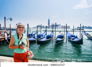 Mature tourist woman travelling in Italy stays against row of gondolas moored by Saint Mark square against San Giorgio di Maggiore church in Venice.