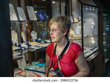 Mature tourist woman travelling in Italy looks at showcase of golden jewellery shop on Ponte Vecchio bridge in Florence, Italy.