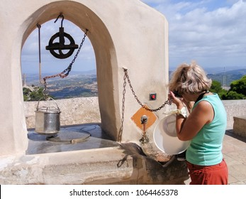Mature tourist woman travelling in Majorca drinks fresh water from old draw well at San Salvador monastery