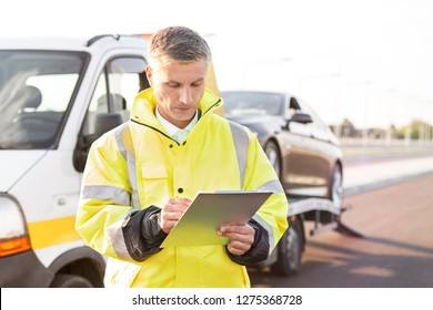 Mature tow truck driver making reports on clipboard against sky