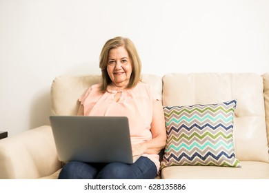 Mature tutor writing her class in her computer sitting in the living room at home