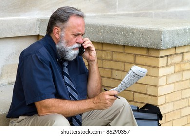Mature unemployed salesman makes a call on his cell phone to reply to a advertisement for a want ad job in the newspaper.