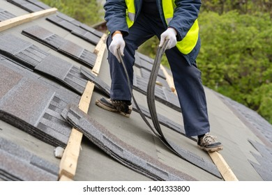 Mature and unrecognizable collar worker or roofer in uniform work wear installing asphalt or bitumen shingle on top of the new roof under construction residential building