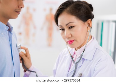 Mature Vietnamese doctor listening to heartbeat of her male patient