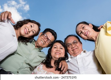 Mature Vietnamese friends embracing and looking at the camera, view from below